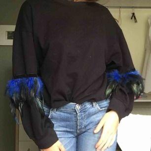 Sweatshirt med fjädrar vid ärmarna som är i mycket bra skick.