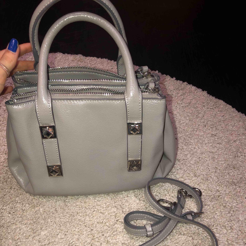 Liten grå handväska från zara, köpt i höstat och inte alls använd mycket så den är i bra skick! Väldigt praktisk då den har tre olika fack. Frakt tillkommer. Väskor.