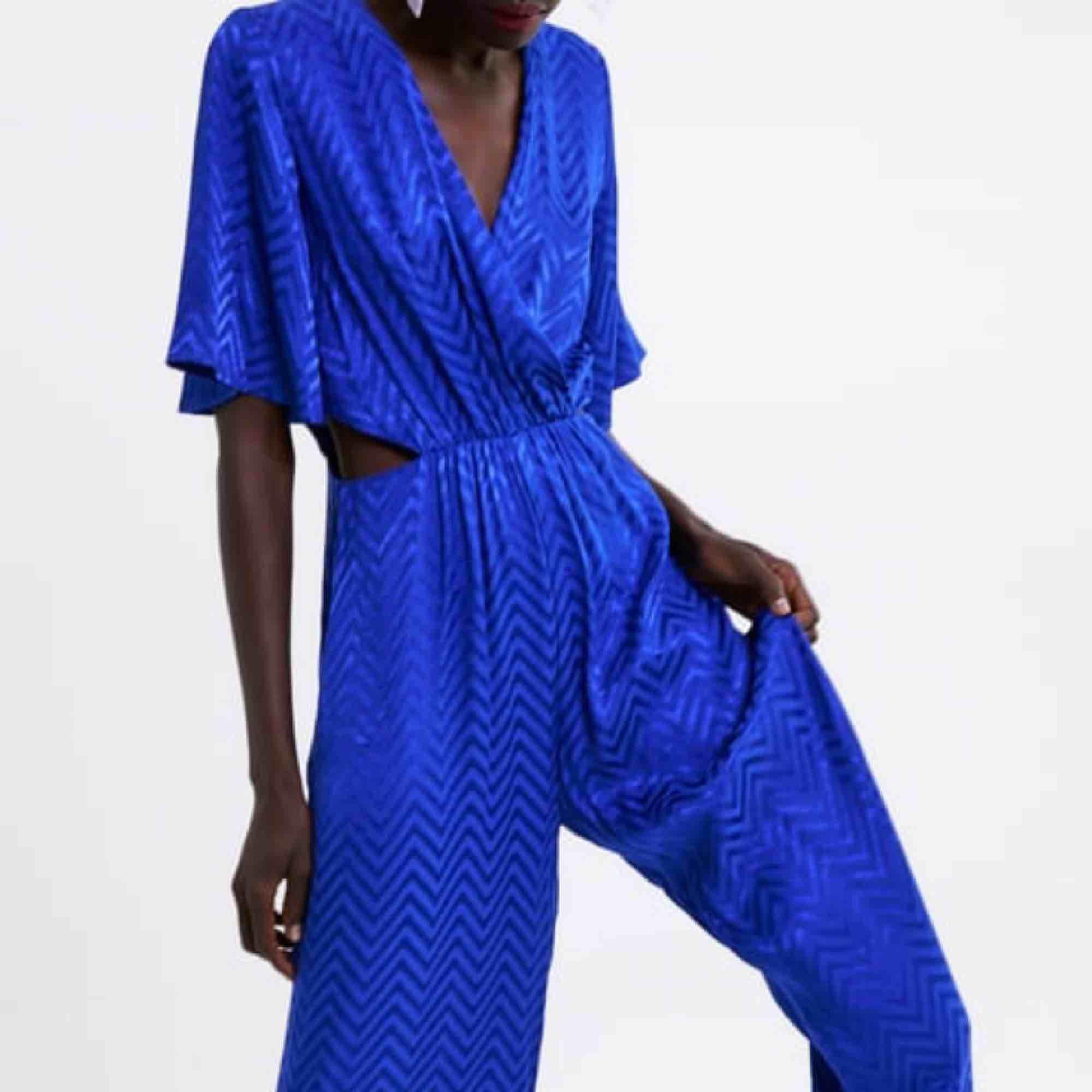 Säljer denna blåa jumpsuit med cut-outs vid midjan. Från zara, oanvänd med lapparna på! Priset är inklusive frakt 😊😊😊. Klänningar.