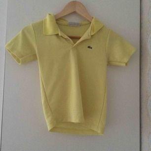 Gul Lacoste-tröja köpt second hand. Ganska säker på att det är en barntröja men skulle passa bra på en 32-34 Frakt 27kr