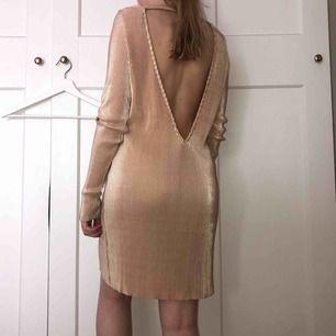 Plisserad klänning i roseguld/champagnefärgad med guldskimmer, storlek S. Använd vid ett tillfälle. Pris diskuterbart.