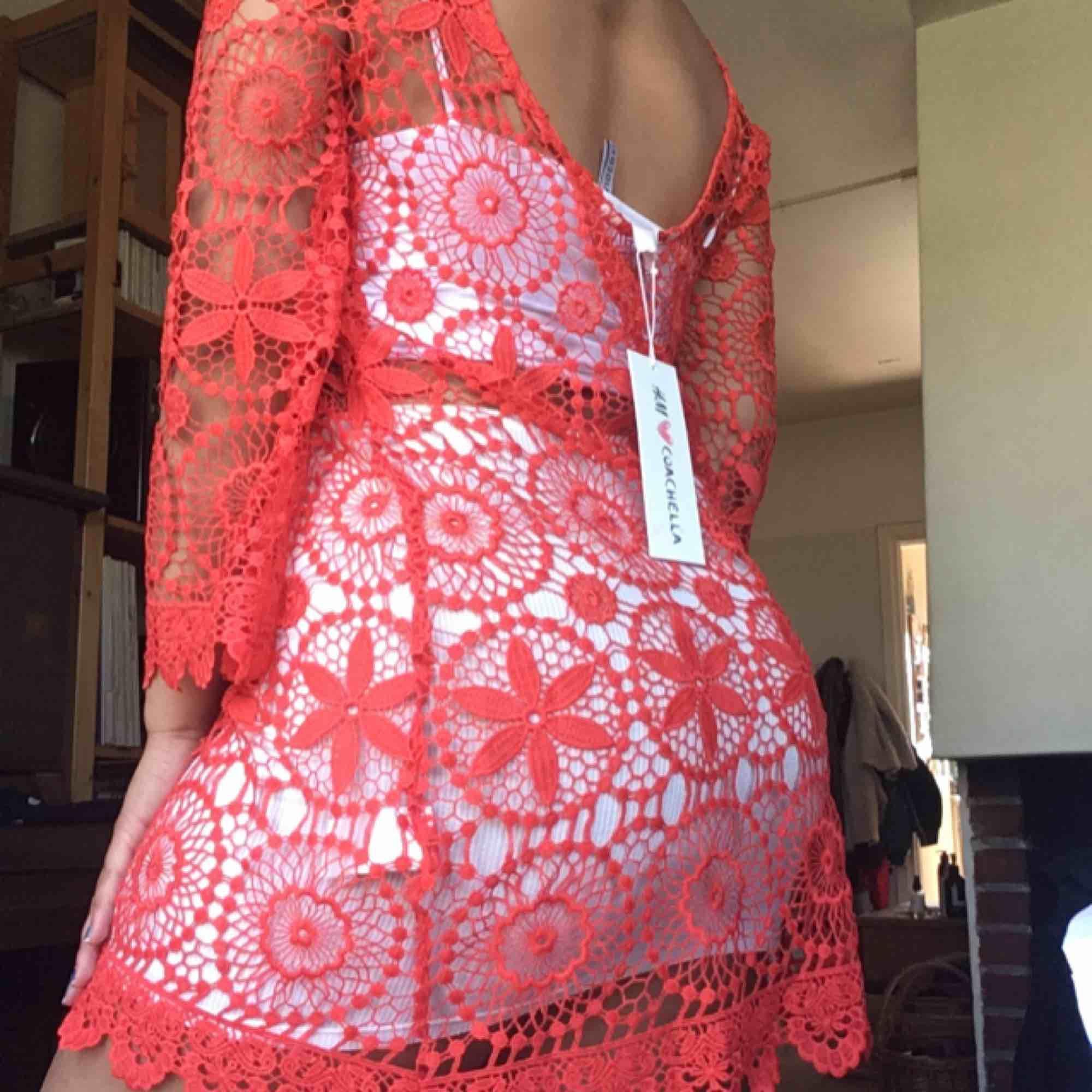 Oanvänd virkad korall/neonig orange klänning från HM Loves Coachella kollektionen. Storlek M, frakt på 40 kr tillkommer :). Klänningar.