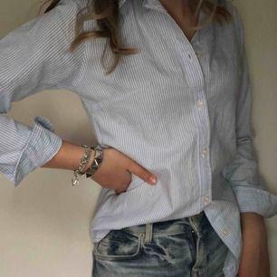Blå och vitrandig klassisk skjorta  Endast använd ett fåtal gånger och mycket överraskad över tröjans kvalité, mycket bra!   Nypris 150kr