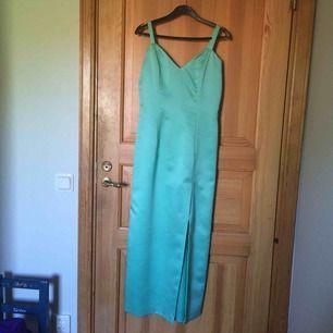 Balklänning i turkos färg. Slitsen börjar på mitten av mitt lår (jag är 165 cm). Köpt på second hand men i väldigt gott skick. Sparsamt använd av mig. Köparen står för frakt! :))
