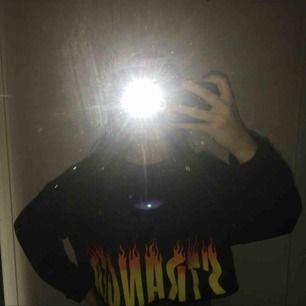Svart tröja med eldtryck som det står stranger på. Stl är L men funkar för S o M om man har oversized