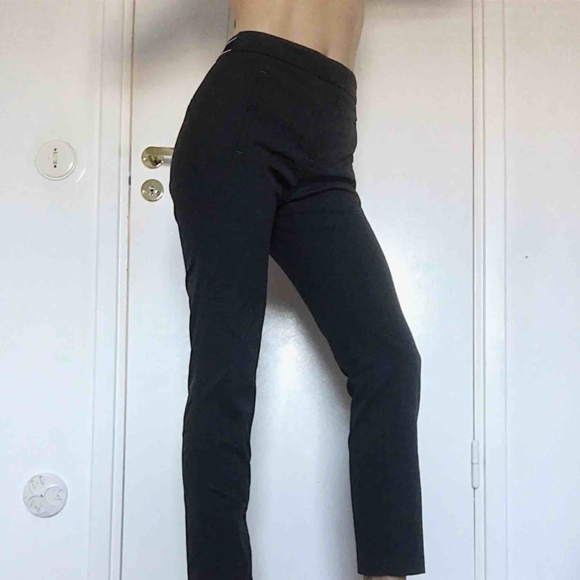 Helt, helt, helt perfekta mörkgrå kostymbyxor med snygg resårdetalj vid baksidan av midjan. Sitter såå bra på alla ställen och är superbra längd! . Jeans & Byxor.