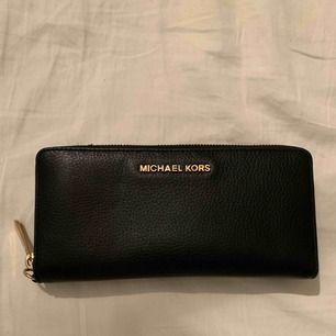 Svart clutch/plånbok från Michael Kors med guldiga detaljer! Använd 1 gång. Kan användas som antingen en mindre clutch eller en större plånbok då den har plats för mobil samt fickor och korthållare etc. Nyskick!