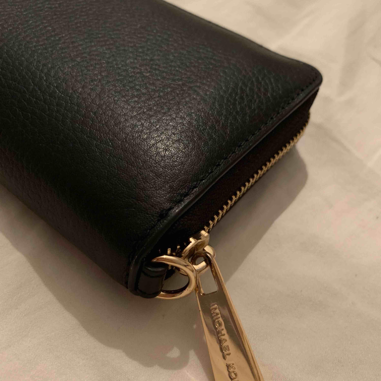 Svart clutch/plånbok från Michael Kors med guldiga detaljer! Använd 1 gång. Kan användas som antingen en mindre clutch eller en större plånbok då den har plats för mobil samt fickor och korthållare etc. Nyskick!. Väskor.