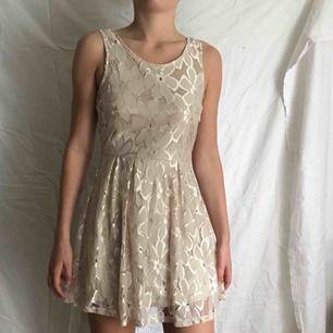 Guldig blommig klänning i stl XS. Använd 1 gång. Frakt ingår i priset.