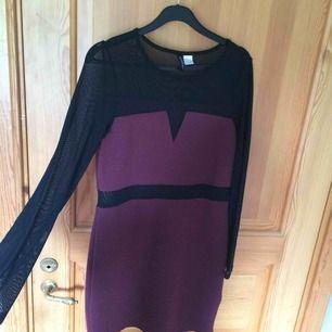 En kroppsåtsittande klänning i vinrött stretch-tyg och svart, genomskinligt tyg. Klänningen slutar strax över mitten av mitt lår (jag är 165 cm). Sparsamt använd. Köparen står för frakt :))