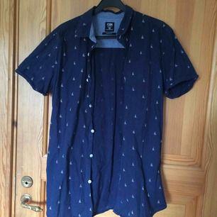 En marinblå skjorta med segelbåtar på. Köpt från herravdelningen på NewYorker. Väl använd men inte på tag. Köparen står för frakten :))
