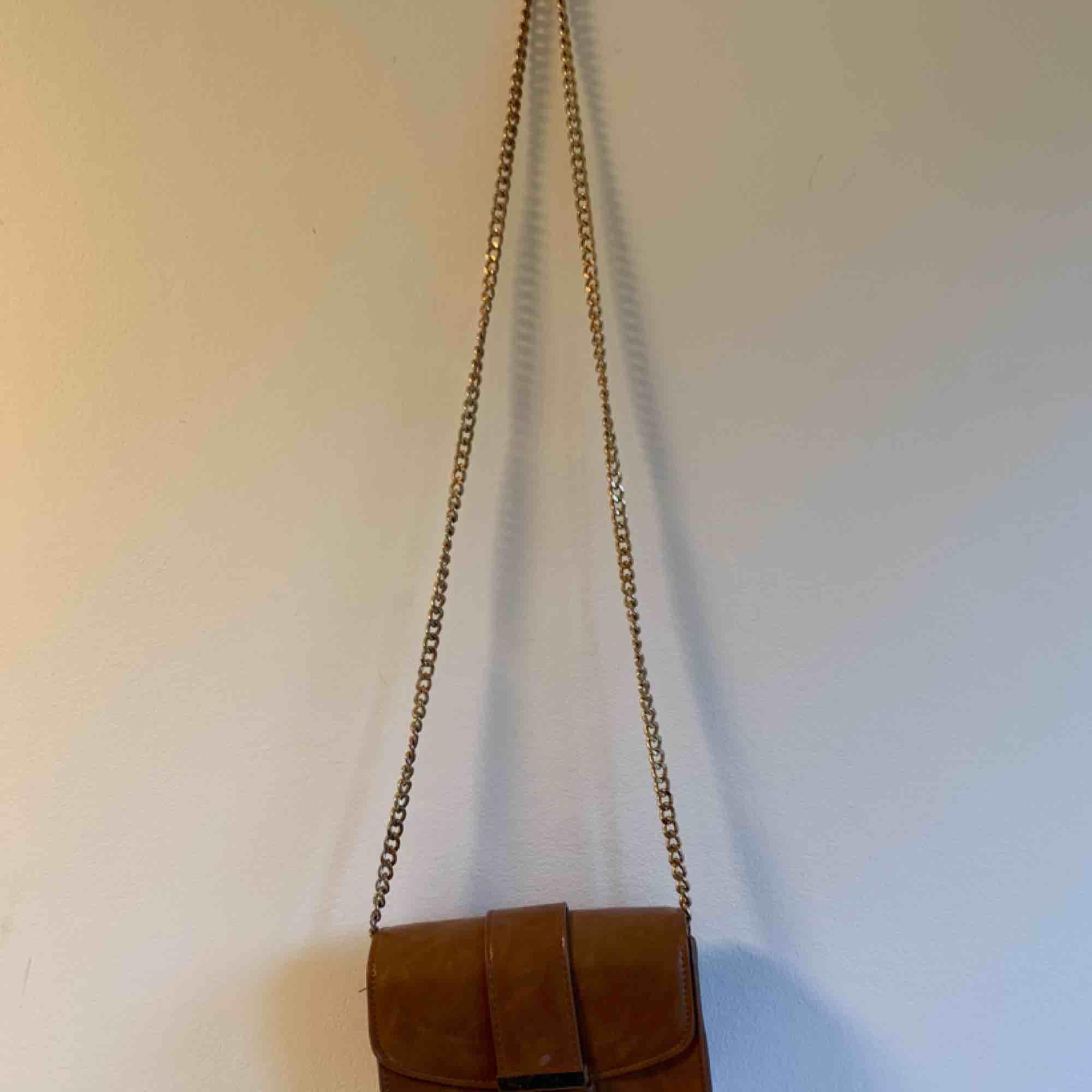 Liten väska i cognac med gulddetaljer. Lite sliten på metallen och i vissa sömmar, därav priset. 🥰. Väskor.