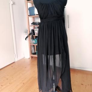 Svart klänning med slit i kjolen. Jag har ingen aning var den kommer ifrån och om den varit använd.