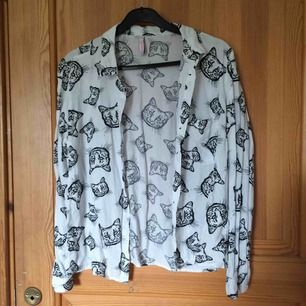 En skjorta med katt-tryck. Köpt från NewYorker och väl använd. Men inte på väldigt länge och den är i gott skick. Passar även S. Köparen står för eventuell frakt :))