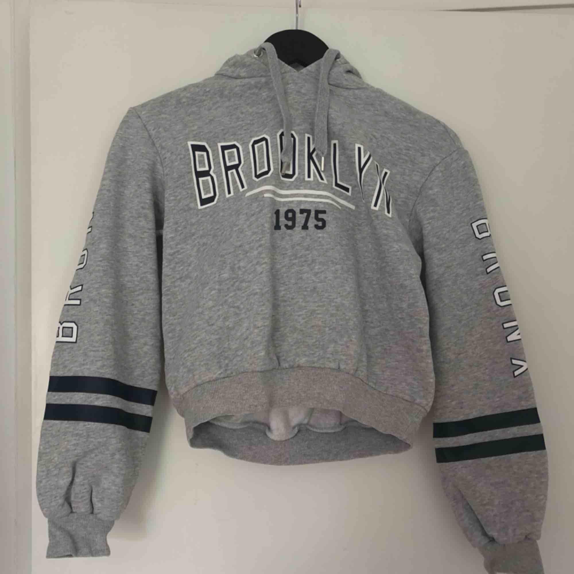 """En cropped hoodie med texten """"Brooklyn"""" på bröstet och """"Bronx"""" på ärmarna. Mjuk och skön insida. 2 snören från luvan. Bra skick. . Huvtröjor & Träningströjor."""