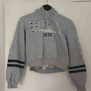 """En cropped hoodie med texten """"Brooklyn"""" på bröstet och """"Bronx"""" på ärmarna. Mjuk och skön insida. 2 snören från luvan. Bra skick."""