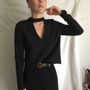 Svart tröja, stl S, kort i modellen. Kragen knyts i bak. Frakt ingår i priset.