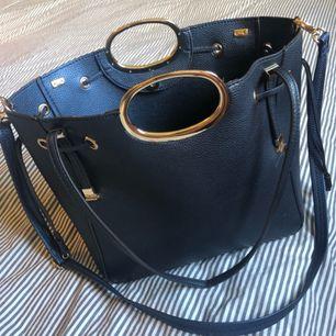 """NY!🌸Rymlig handväska i """"neverfull"""" modell, skinnimitation, marinblå med gulddetaljer. Inga som helst defekter. Köpare betalar ev. frakt."""