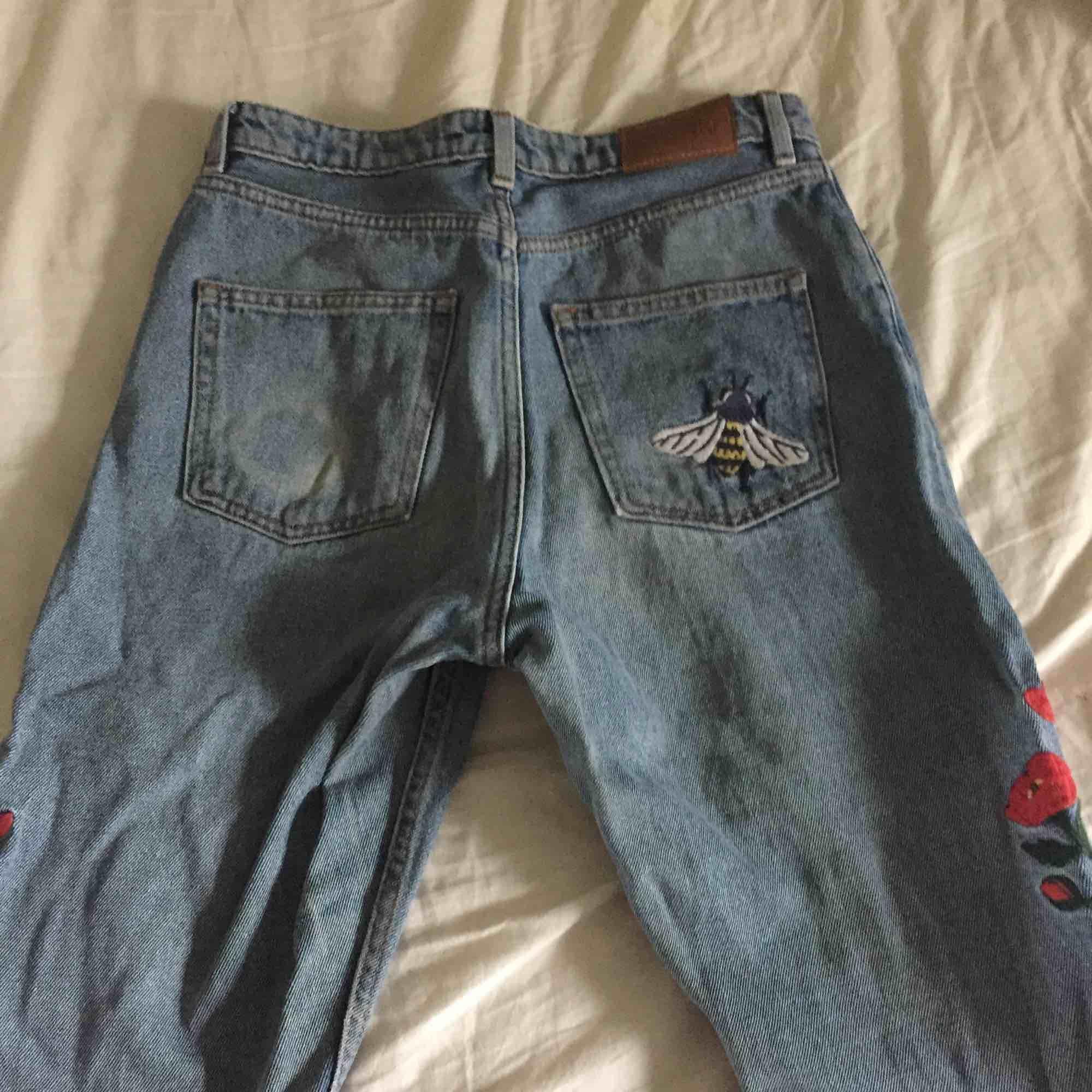 mom jeans från Monki med blommor som detaljer. välanvända men hela. nypris 349kr(?). frakt tillkommer.. Jeans & Byxor.