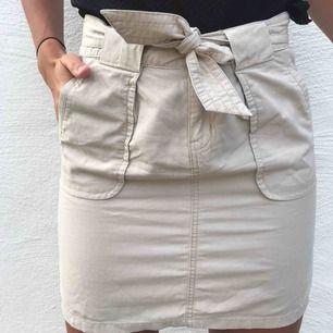 Beige kjol med knytning upptill. Knappt använd, bra skick.