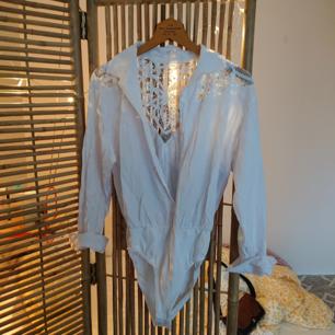 Vintage body i skjortmodell med väldigt fin spetsdetalj i ryggen. Knäppningen nertill sitter mycket bra! I fint skick!