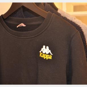 En svart kappa sweatshirt med vit och gul logga. Storlek medium.