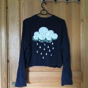 En marinblå tröja med glitterbroderat regnmoln. Väl använd men i gott skick. Köparen står för frakt :)