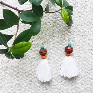Handgjorda örhängen med vita toffsar och färgglada träpärlor!