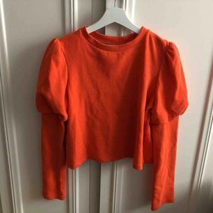 Orange/röd sweatshirt med ballongärmar, lite kortare i modellen,