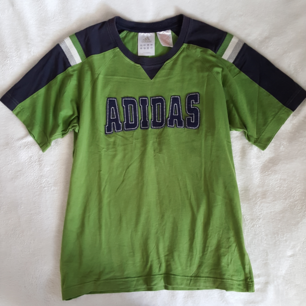 Vintage grön Adidas t-shirt i fint skick. Står storlek 164 på lappen men är som ca storlek S/M. Kan skickas om köparen står för fraktkostnaden som blir 36kr.