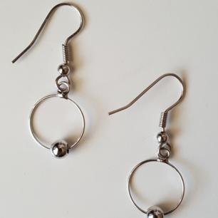 Silverfärgade örhängen i metall. Kan skickas om köparen står för fraktkostnaden, som blir 9kr.