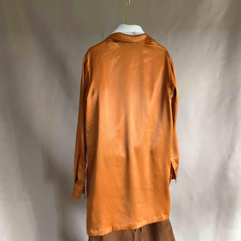 Orange/skimrande Skjortklänning i gott skick från na-kd. Vid fler intressenter går köpet till den som budar högst. Klänningar.