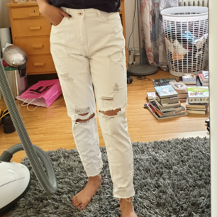 Ett par rippade vita mom jeans.