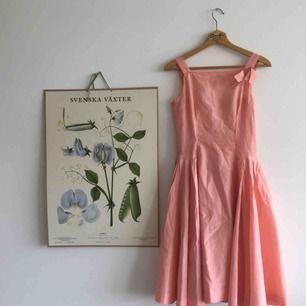 Rosa vintageklänning med figurnära överdel, markerad midja och härligt med volym i kljolen. Snäv över bysten, så passar bäst person med liten byst. Hel och ren men delvis sliten, därav det låga priset. (Se fläck på sista bilden)