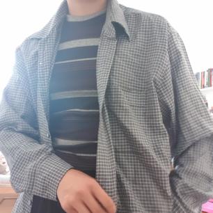 Svart, vit och grårandig skjorta, icke flanell.