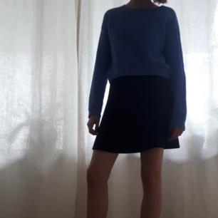 En blå stickad tröja från cubus. Rätt kort jämfört med ärmarna