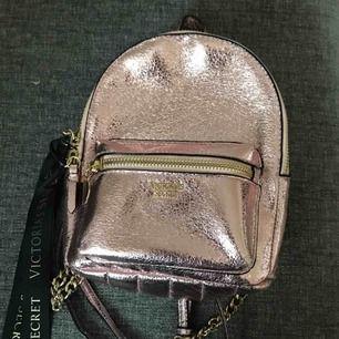 Liten victoria's secret ryggsäck, använd ett fåtal gånger. Banden går att justera.  Nypris: ca 500 kr  Färg: rosé med gulddetaljer Köpt: London