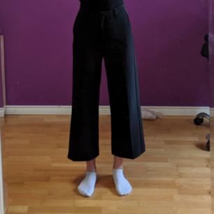 Svarta ankel korta kostym byxor i storlek 36. Det finns möjlighet att sätta i skärp i byxorna då de är lite stora i midjan.