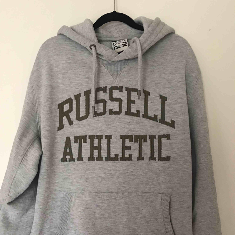 Grå Russel Athletic hoodie med grön text. Bra skick. Priset kan diskuteras, köparen står för frakten . Huvtröjor & Träningströjor.