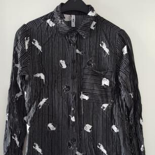 Svart skjorta med katter på i jättefint skick. Storlek XS men tror den passar S med. Kan skickas om köparen står för frakten som blir 36kr.