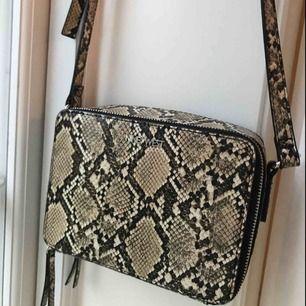 Superfin liten handväska/axelbandsväska i snakepattern (vilket är fett hett ;),) som ny! Väskan är hård och därför väldigt rymlig med justeringsbart axelband.