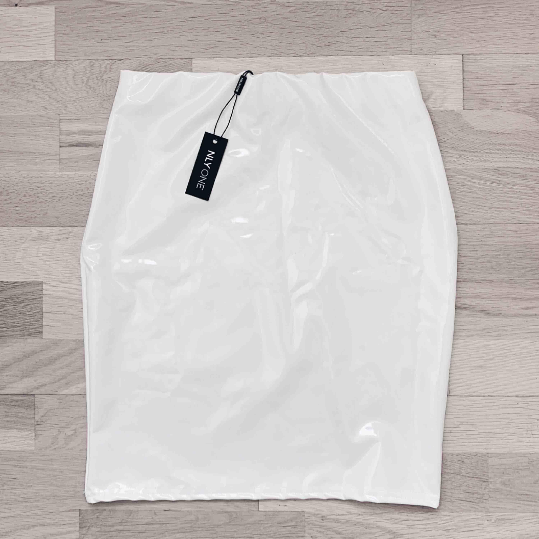 Supersnygg vit latex kjol från Nelly.com! Helt oanvänd med lapp kvar. Frakten ingår i priset✨. Kjolar.
