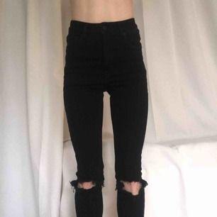"""Cheap Monday jeans, """"high skin"""". Svarta med slitningar på knäna, superstretchiga och sköna.  Avklippta och är mer som 26/32 (lappen säger 26/34).  Material: organisk bomull Oanvända, nyskick. Passar Strl 25-27 (midja)."""