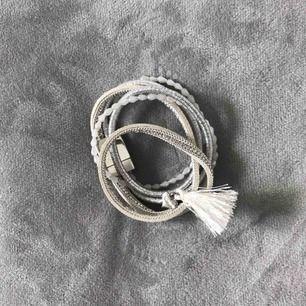 Nytt armband GEMINI by helen. Silverfärgade detaljer, skinnimitation, vit, benvit, strass, pärlor, tofs och hjärta. Magnetlås, total längd 37,5cm, viras runt handleden. Köpt på Drömhuset Sthlm, nypris 290kr, aldrig använt