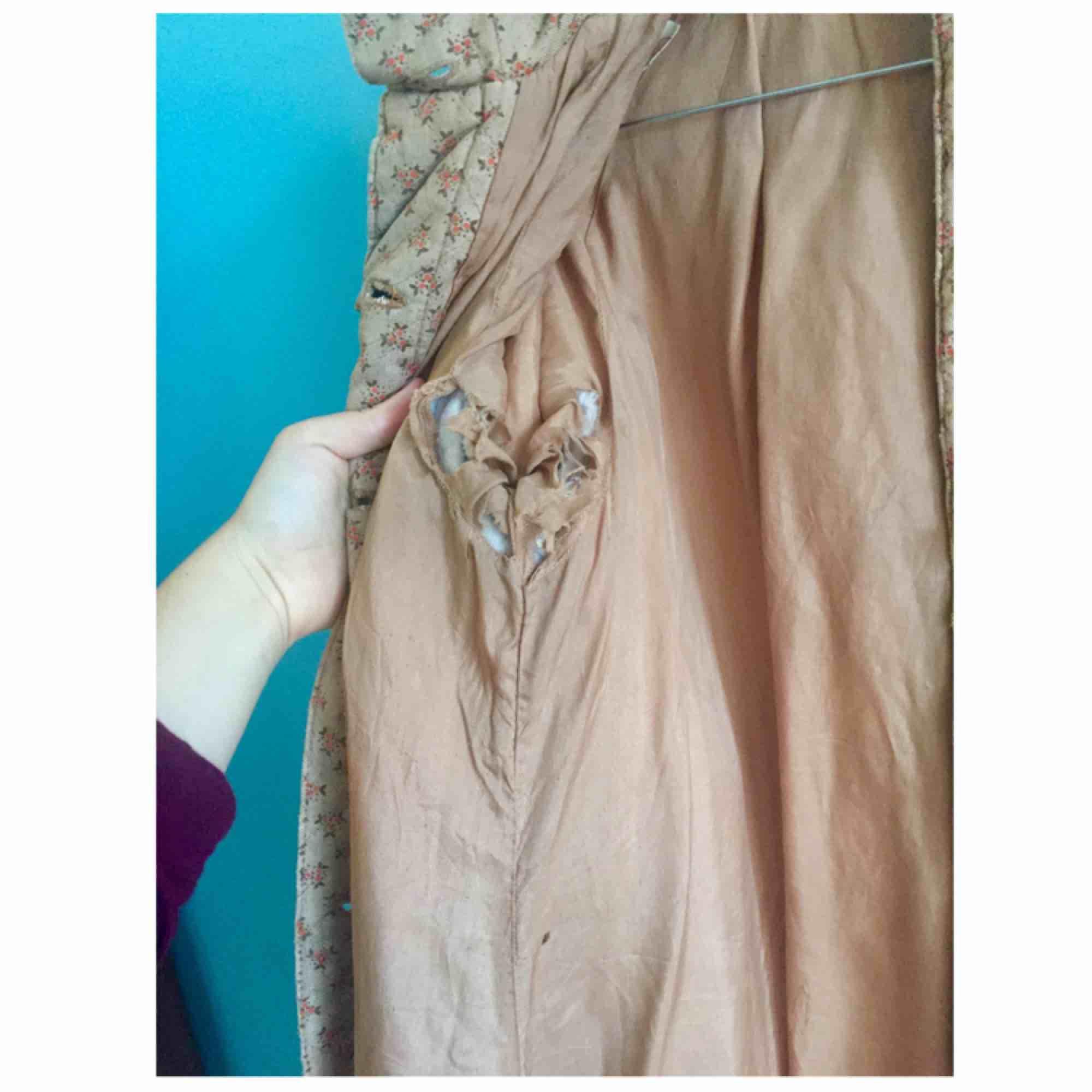 Vårkappa Gudrun Sjödén XS/S. Behöver en restaurering då fodret och ena fickan är trasigt (se bild 3) samt saknar några knappar. Kan skicka mer bilder om så önskas!   Hoppas någon vill fixa till denna fina jacka så att den får bli använd! . Jackor.