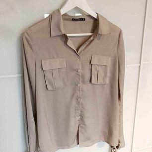 Super fin beige skjorta i lite silke liknande material, knyts i armarna med band
