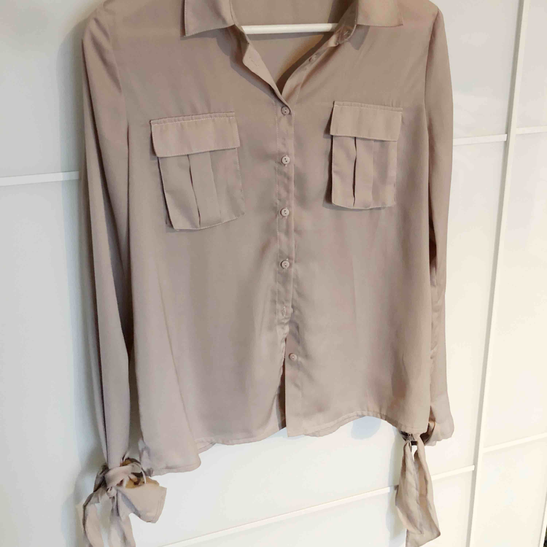 Super fin beige skjorta i lite silke liknande material, knyts i armarna med band. Blusar.