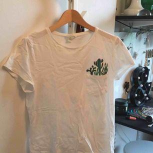 Vit t-shirt med ficka och kaktusar, använder inte