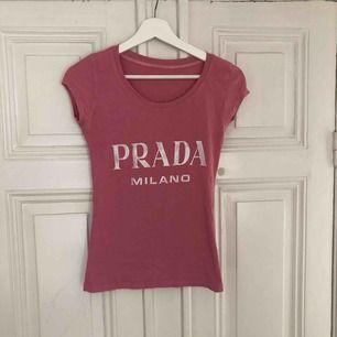 """Säljer en rosa """"Prada"""" tröja med trycket prada Milano  Modellen är figursydd och sitter tajt. Bra skick bara att trycket är lite rispigt (framkommer på bilden) Annars en jätte fin tröja som jag hoppas kommer till användning hos nån annan"""