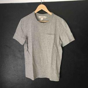 Grå H&M t-shirt med ficka på framsidan. Nyskick.